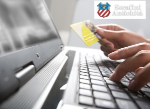 Image of hands holding credit card and pressing a keys of keyboard